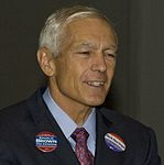 Wesley Clark wearing buttons for Charlie Brown's congressional and Rick Noriega's senatorial campaigns at Netroots Nation 2008 (2680986222).jpg