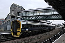 A two coach train beneath a lattice bridge