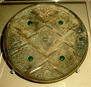 Zhou/ Han bronze mirror with glass inlays, said to incorporate Greco-Bactrian artistic patterns (rosette flowers, geometric lines, and glass inlays). 300-200 BCE. Victoria and Albert Museum.