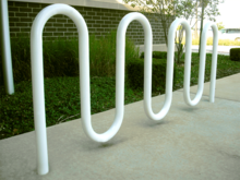 A white-painted round metal tube bent into a double M shape and set in concrete in front of a grassy verge and a brick wall.