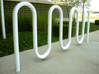 Выкрашенная в белый цвет круглая металлическая труба, изогнутая в форме двойной буквы М и вставленная в бетон перед травянистым краем и кирпичной стеной.