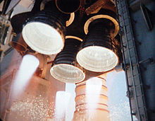 Three bell-shaped rocket engine nozzles projecting from the aft structure of a Space Shuttle orbiter. The cluster is arranged triangularly, with one engine at the top and two below, with two smaller nozzles visible to the left and right of the top engine. The three larger engines are firing, with white-hot flames visible projecting from each nozzle. The Space Shuttle's left solid rocket booster (a white, cylindrical rocket) is visible in the background, with the two large, grey tail service masts visible to the left and right of the orbiter's aft structure.