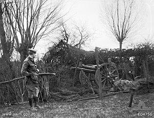 1st Regiment, Royal Australian Artillery - Two Australian soldiers and an officer, at a camouflaged gun position of the 1st Australian Field Artillery Brigade.