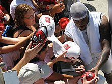 African American male in stocking cap signs autographs for fans on footballs