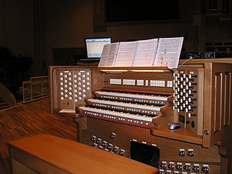 Electric organ - A custom three-manual Rodgers Trillium organ console installed in a church. Note the sound module (Rodgers MX-200 on right top) for extra pipe and orchestral sounds, and the laptop (left top) used for sequencing the organ