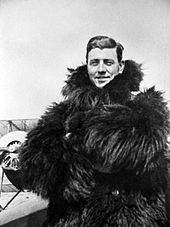 Half-length informal portrait of man in thick fur coat with a biplane in the background