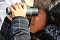 A young girl uses binoculars for the first time to watch the seagulls at Monterey State Beach. (32986504481).jpg