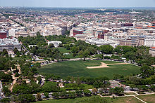 The White House appears in the upper left and the perimeter fence in front of Constitution Avenue is in the lower right, with an enormous green field separating them: The Ellipse.