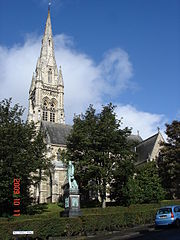A stone church seen from a slight angle at the southwest, with a tower and tall spire on the left and the body of the church extending to the right