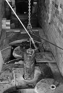 Chainfall and metal flanged, closed cylinder being lowered into a hole