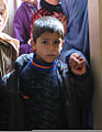 An Afghan boy waits with his mother for his turn to receive school supplies during Operation School Supplies Nov. 10, 2011, at Bagram Airfield, Afghanistan 111110-A-DY116-003.jpg
