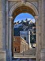 Arco di Traiano visto attraverso l'Arco Clementino.JPG