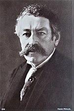 Zwart-wit portret van een besnorde man met grijzend haar, met stropdas en driedelig pak