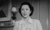 An attractive young Japanese woman, wearing a white blouse, is shown talking, photographed from below; a lamp, some bottles on a mantlepiece and part of a painting are visible in the left background.