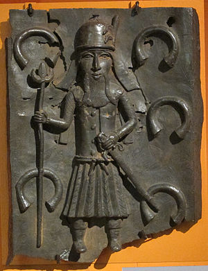Manilla (money) - A Benin Bronze depicts a Portuguese soldier with manillas in the background
