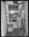 Betty, daughter of J.F. Bryant, miner, watering flower in hallway entrance to the upstairs flat in which the family... - NARA - 540734.tif