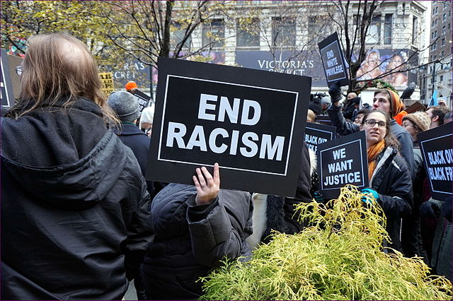 """Protester holds up """"End Racism"""" sign at New York City Black Lives Matter rally."""