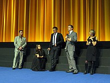 Scott Franklin, Mila Kunis, Vincent Cassel, Darren Aronofsky, and a moderator stand on a stage with a golden curtain backdrop wearing formal attire and discussing Black Swan