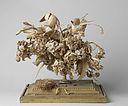 Bloemenruiker van geknipt papier met vogelnestje, onder stolp.