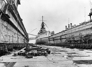 A view of a large warship from the floor of a dry dock