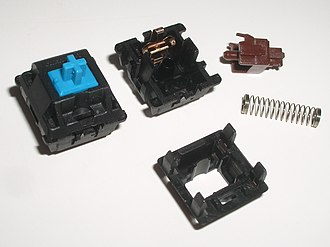 Keyboard technology - Cherry MX blue mechanical switch (left) and disassembled MX brown switch (right).