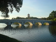 the bridge connecting the chinese garden and japanese garden islands the pagoda is seen rising behind it