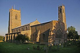 View of the church bathed in early morning sunlight.  There is a large tower at the further end, and a small tower beside the chancel.