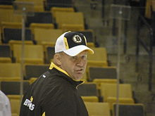 Photo de Claude Julien de 3/4 dos portant la casquette des Bruins.