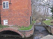 Close view of the south side of the building.  A small eliptical brick arch leads the water into the enclosed millrace, and there is an overflow weir to the right of the building. Trees are visible on the riverbank beyond.  The water is constrained in a red brick channel with a bulnose (curved) corner.  Two scroll shaped iron 'plates' are on the upper wall, terminals for tie-rods that pass through the building. This is a winter view, and the state of the trees makes this stark. There is a small and unturbulent flow of water through the overflow weir, because the level is accurately controlled by the main weir in the old lock chamber. A precarious plank bridge, with no handrails, crosses the overflow race to reach the lockside on the right.