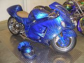 An motorcycle with fully enclosed bodywork painted in iridescent blue with flames, and a helmet painted in the same color scheme, with a matching blue fur crest on the helmet.