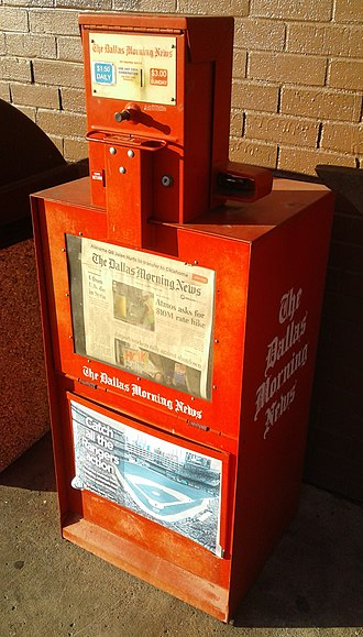 The Dallas Morning News - Newspaper vending machine with copies of The Dallas Morning News, in front of a restaurant in northeast Dallas, 2019.