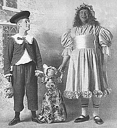 two men dressed as a boy and a girl hold the hands of a rag-doll between them