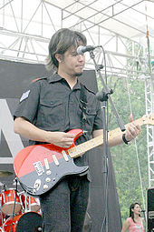 An Indonesian man with long hair, playing a red guitar. His face is partially obscured by a microphone.