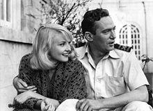 Image en noir et blanc tirée du film Passage Home; Finch a le bras passé autour des épaules de Cilento; ils regardent tous les deux vers la droite; Finch est en train de parler.