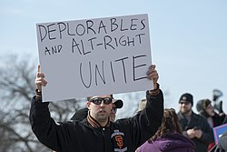 "A man holds up a sign saying ""DEPLORABLES AND ALT-RIGHT UNITE"" with a cartoon frog in the corner."