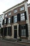 foto van Pand met brede lijstgevel van vier vensterassen, parterre met twee verdiepingen, middenrisaliet en hoekpilasters