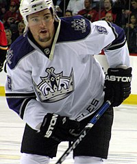 Hockey player in white and dark blue uniform. He crouches to his right, holding his stick across him.