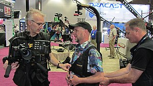 Electronic news-gathering - Easyrig Inventor Johan Hellsten with DP Mark Schulze wearing Easyrig at NAB 2015