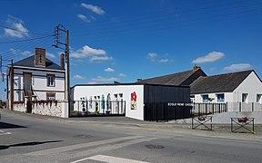Photographie en couleurs d'un ensemble de bâtiments avec une cour close d'une grille portant la mention «ECOLE RENE CASSIN».