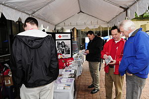 Food distribution - An American Red Cross volunteer explains a program to people visiting their display during FEMA's Hurricane Awareness Day.