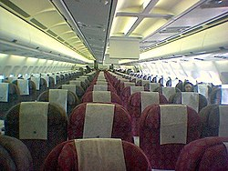 Interior of a Qatar Airways Airbus. A couple of video Systems (the vertical white panels) are visible above the very centre seats of the aircraft