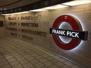"Words mounted on a cream-coloured stone wall next to a large, illuminated London Underground symbol (red ring with a blue bar) with the words ""Frank Pick"" on the blue bar"