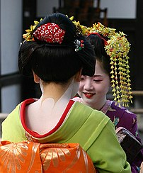 2 Geisha conversing near the Golden Temple in Kyoto, Japan. Parts of the kimono and the special make-up are clearly visible.