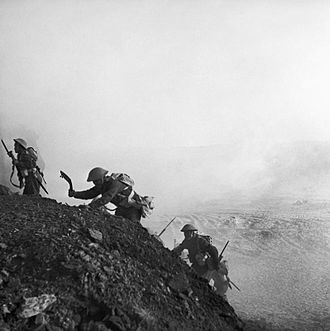 4th Infantry Division (India) - Ghurkhas advance through a smokescreen up a steep slope in Tunisia, 16 March 1943.