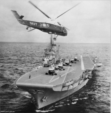 A small aircraft carrier is sailing towards the frame, with five helicopters in a line on the carrier's deck. A sixth helicopter hovers in the foreground