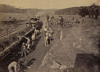 """Herman Haupt - The locomotive, """"General Haupt"""" is being used for work detail while its namesake, Herman Haupt, stands on the hill to the right inspecting railway work near Bull Run in 1863"""