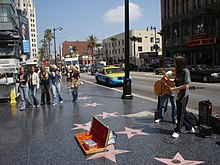 Several stars on the Walk of Fame at 6801 Hollywood Boulevard, with اجرای خیابانی and passersby