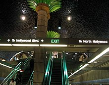 An escalator and a flight of stairs which reflect turquoise light. A large imitation palm tree is located between the escalator and the stairs.