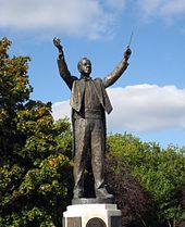 outdoor full length statue showing Holst conducting