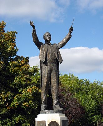 Gustav Holst - Statue of Holst at his birthplace, Cheltenham. He is shown with the baton in his left hand, his frequent practice because of the neuritis in his right arm.